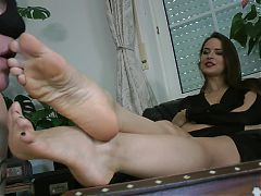 Slave sucks and licks the feet of the beautiful mistress